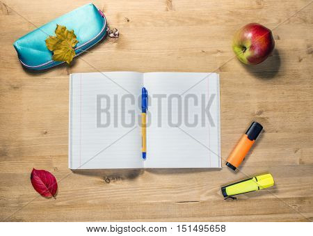 Workspace of the student with opened copybook, case, pen, apple, markers on desk.
