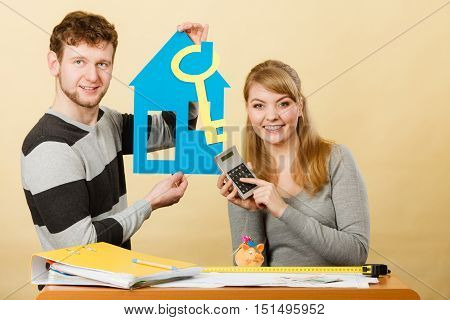 Real estate ownership finance concept. Couple with house and calculator. Young man and woman holding cutouts of home and key.