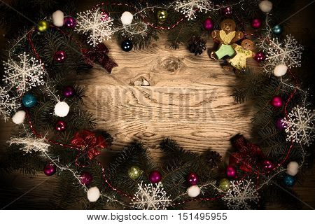 green fir branches on the wooden floor with darkening at the edges with Christmas decorations