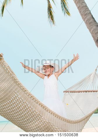 little girl child swinging in hammock on the beach eyes closed sea ocean
