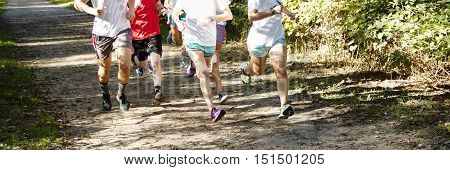 Runners training in a group for cross country in the woods on a dirt path