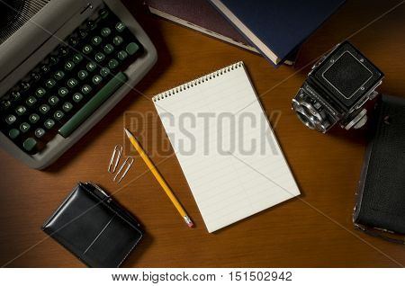 poster of Blank steno notepad on a wooden desktop among vintage journalism props including a typewriter and film camera