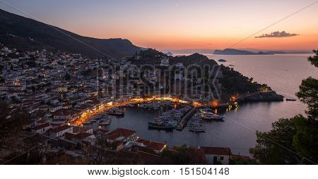 Top view twilight of Hydra island, Greece - city center and yaht marina after sunset.