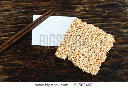 Chopsticks noodles on  old wood and note paper.