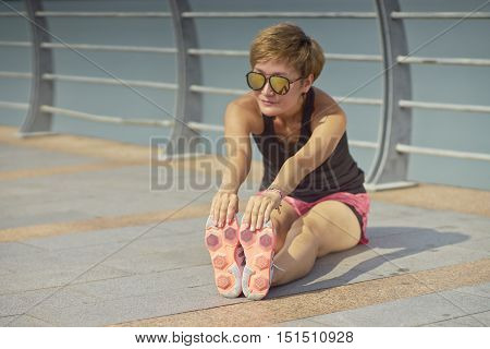 Young Woman Stretching Before Jogging In City Park