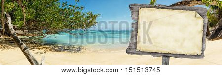 Empty wooden board with old paper for copyspace placed on beautiful tropical beach at Seychelles. Concept fro travel and vacation