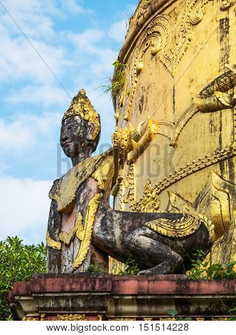 Detail of old pagoda at the Moe Hnying Monastery in Yangon Myanmar. Sculpture of hybrid creature with human head and animal body in the foreground.