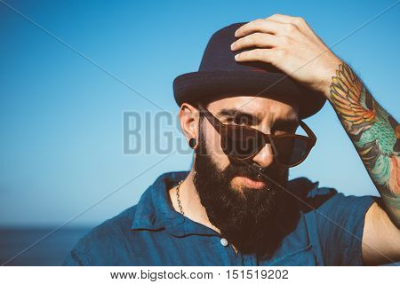 Portrait of stylish bearded man with colorful tattoo on hand lookig over sunglasses and holding hat
