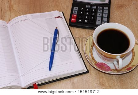 Office workstation, Cup of coffee , tablet and white papers the table. The table of a businessman, a businesswoman. The view from the top.