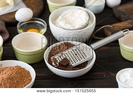 Different ingredients for making chocolate cake. Bowl grater chocolate cocoa flour egg and butter on a dark wooden table front view with copy space