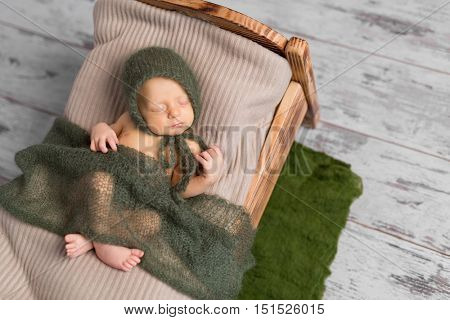 cute sleeping newborn baby in hat on little bed covered with blanket