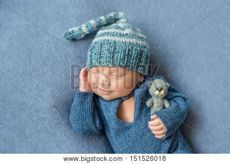 smilimg sleeping newborn boy in blue suit and hat with toy in hand