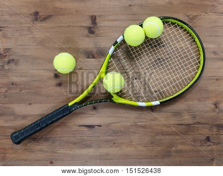 Sporty tennis racket with balls on wooden table