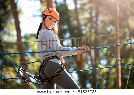 Having a great time. Nice joyful confident woman wearing special equipment and following the rope way while having fun in the adventure park
