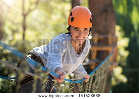 Pleasant climbing activities. Active confident beautiful woman standing on the rope way and leaning forwards while spending her time in high wire park