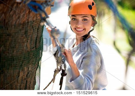 Pleasurable moments. Brave young elated woman holding the ropes and looking at you while climbing in the adventure park