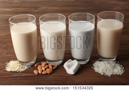 Glasses of almond, rice, sesame and coconut milk on wooden table