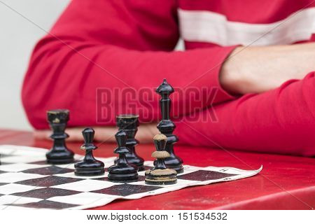 Man in red is contemplating and playing chess in old chessboard