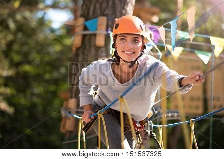 On the high ropes course. Attractive optimistic brave woman leaning forwards and holding on to the ropes while climbing on the rope ladder