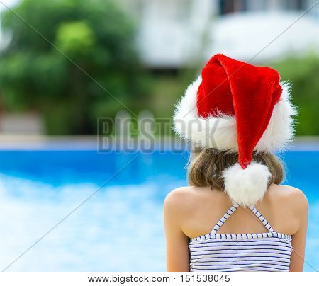 Lonely Little Girl Sitting Near The Pool In Red Christmas Hat.