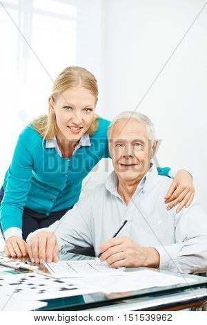 Family with senior man solving crossword puzzle at home for memory training