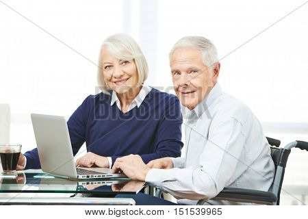 Senior couple with laptop computer using ecommerce online shopping in the internet