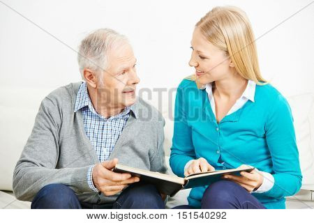 Granddaughter and grandfather watching photos together in a photo album at home