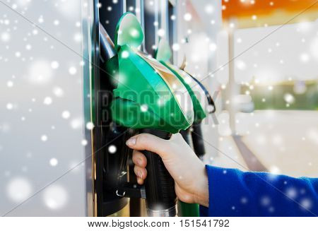 winter, fuel, oil, tank and transport concept - close up of hand holding gasoline hose at gas station over snow