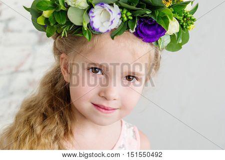 Portrait of a cute little girl in a wreath of flowers