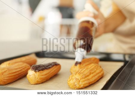 Decorating delicious homemade eclairs with chocolate on baking tray