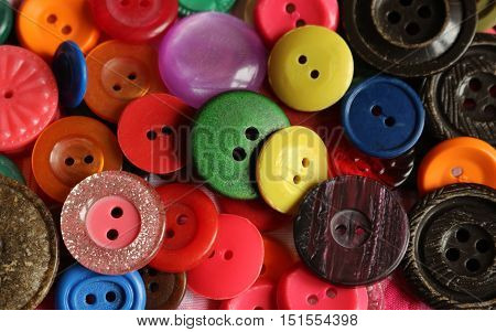 Mixed color bright buttons filling the frame as background.Sewing accessories.