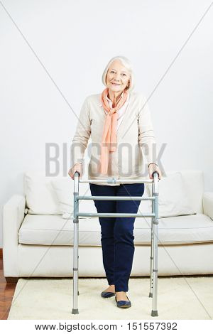 Smiling senior woman standing with walker at home in living room