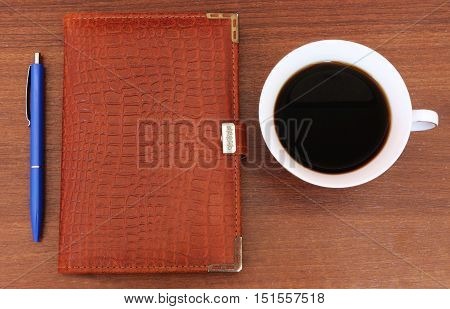 Office workstation, Cup of coffee , Notepad and pen on the table. The table of a businessman, a businesswoman.