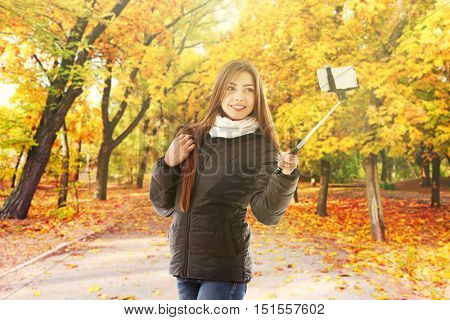 Young woman taking selfie on blurred city park background.