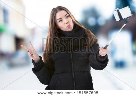 Young woman taking selfie on blurred city street background.