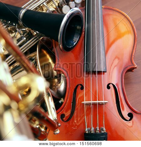 Close up of musical instruments - violin,clarinet, saxophone and trumpet on a wooden surface