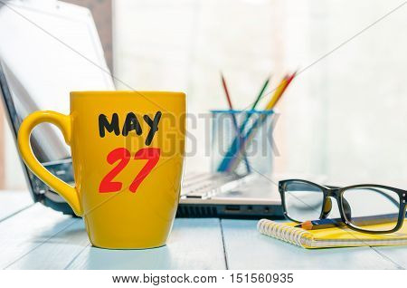 May 27th. Day 27 of month, calendar on morning coffee cup, business office background, workplace with laptop and glasses. Spring time, empty space for text.