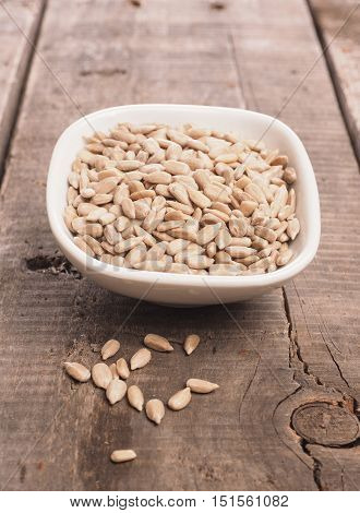 Sunflower seeds in a white bowl on a rustic wooden table