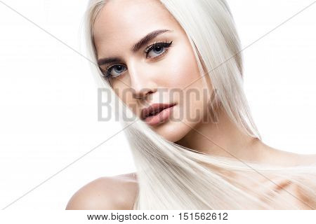 Beautiful blond girl in move with a perfectly smooth hair, and classic make-up. Beauty face. Picture taken in the studio.