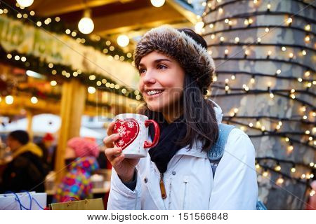 Happy young woman drinking hot drink at christmas fair, smiling, looking away.