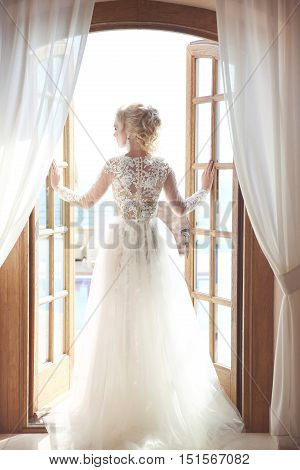 Young Bride In Gorgeous Wedding Dress With Voluminous Skirt Looking At Window, Indoors. Blonde Young