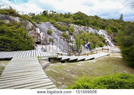 Young active father with little daughter in a back carrier standing on wooden walkboard and observing Thermal area Orakei Korako in New Zealand