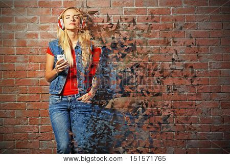 Young woman listening to music in headphones on brick wall background. Creative music concept.