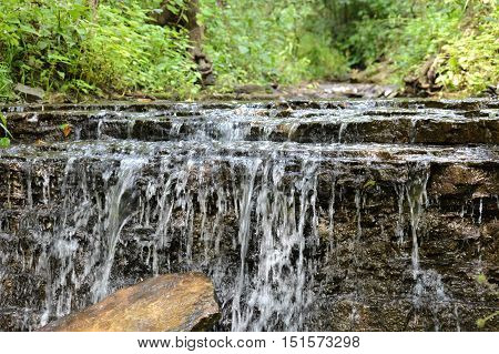 A waterfall in the woods during the summer