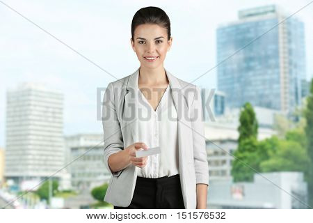 Businesswoman giving business card on blurred city building background. Lawyer and notary concept.