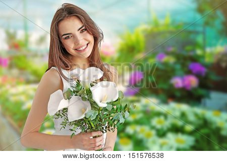 Beautiful young woman holding bouquet of callas on flower shop background