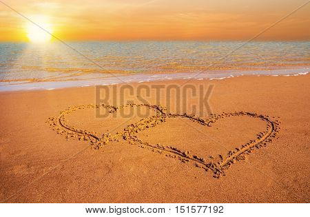 two hand drawn hearts on beach sand over sunset