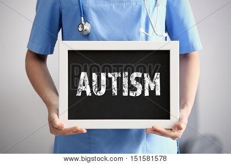 Children autism concept. Female doctor with blackboard, closeup