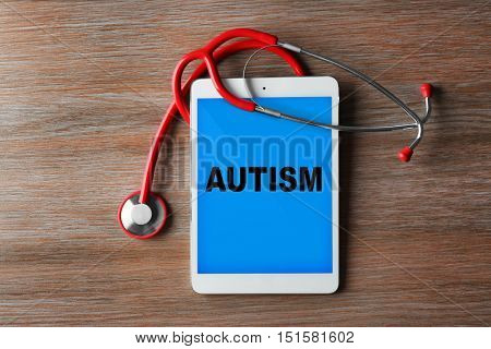 Children autism concept. Red stethoscope and tablet on wooden background