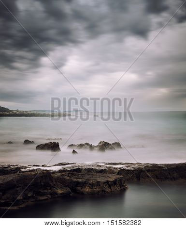 Peaceful Winter Seascape. Cold Sea or Ocean with Dramatic Sky. Long Exposure. Calm Water and Moody Sky. Cold Mysterious Tranquility Concept. Toned Photo with Copy Space.